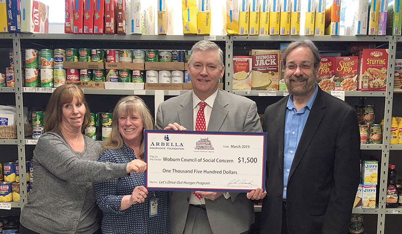 Peter J. Lennon, President and Founder of Lennon Insurance, presents a check for $1,500 to representatives of The Woburn Council of Social Concern. Pictured from left to right are Julia Guthro, Debbie Pisari, Peter Lennon and Dean Solomon